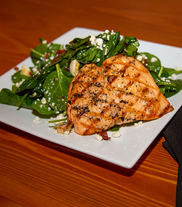 Grilled salmon adds protein to a delicious spinach salad with goat cheese, marinated portabella, roasted red peppers and crispy pancetta tossed in a warm bacon balsamic dressing.