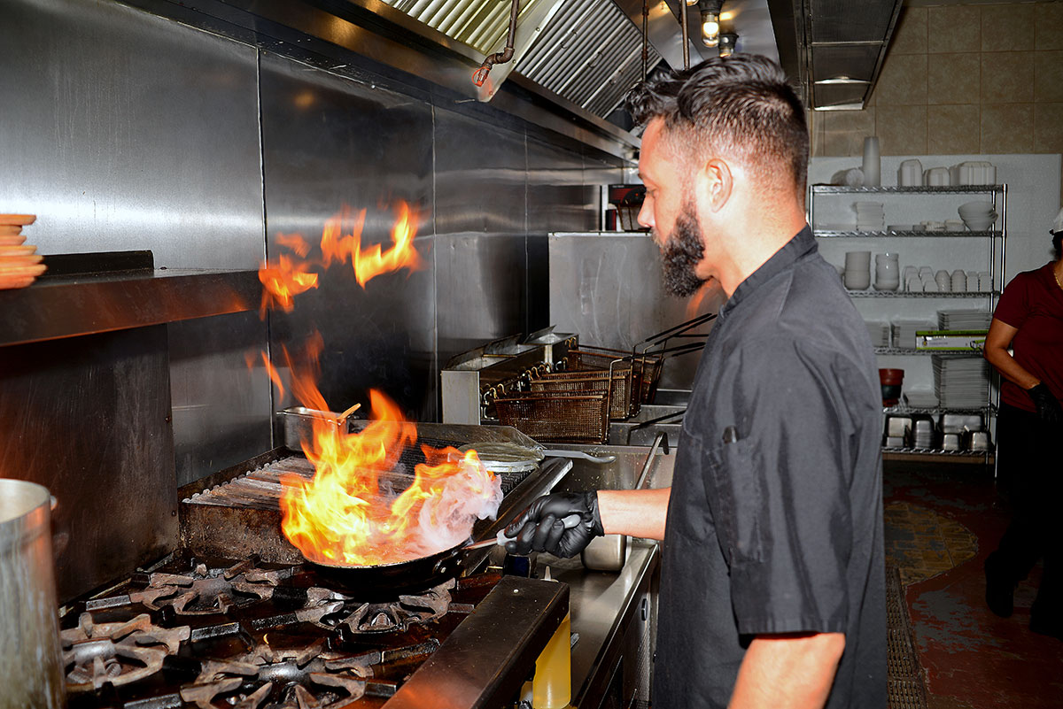 Chef Manuel Acevedo puts flame to one of Dom Rico's specialties, a churrasco, grilled skirt steak, with chimichurri in the open-air kitchen.