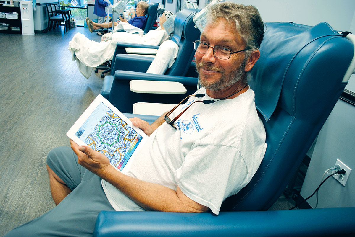 John Steak occupies his time while getting a transfusion.
