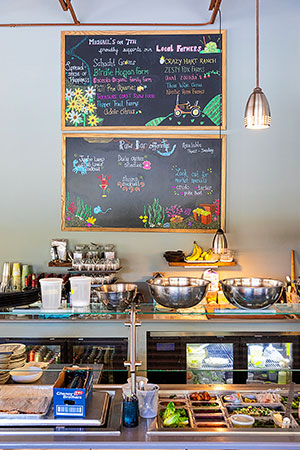 A chalkboard above the salad preparation area