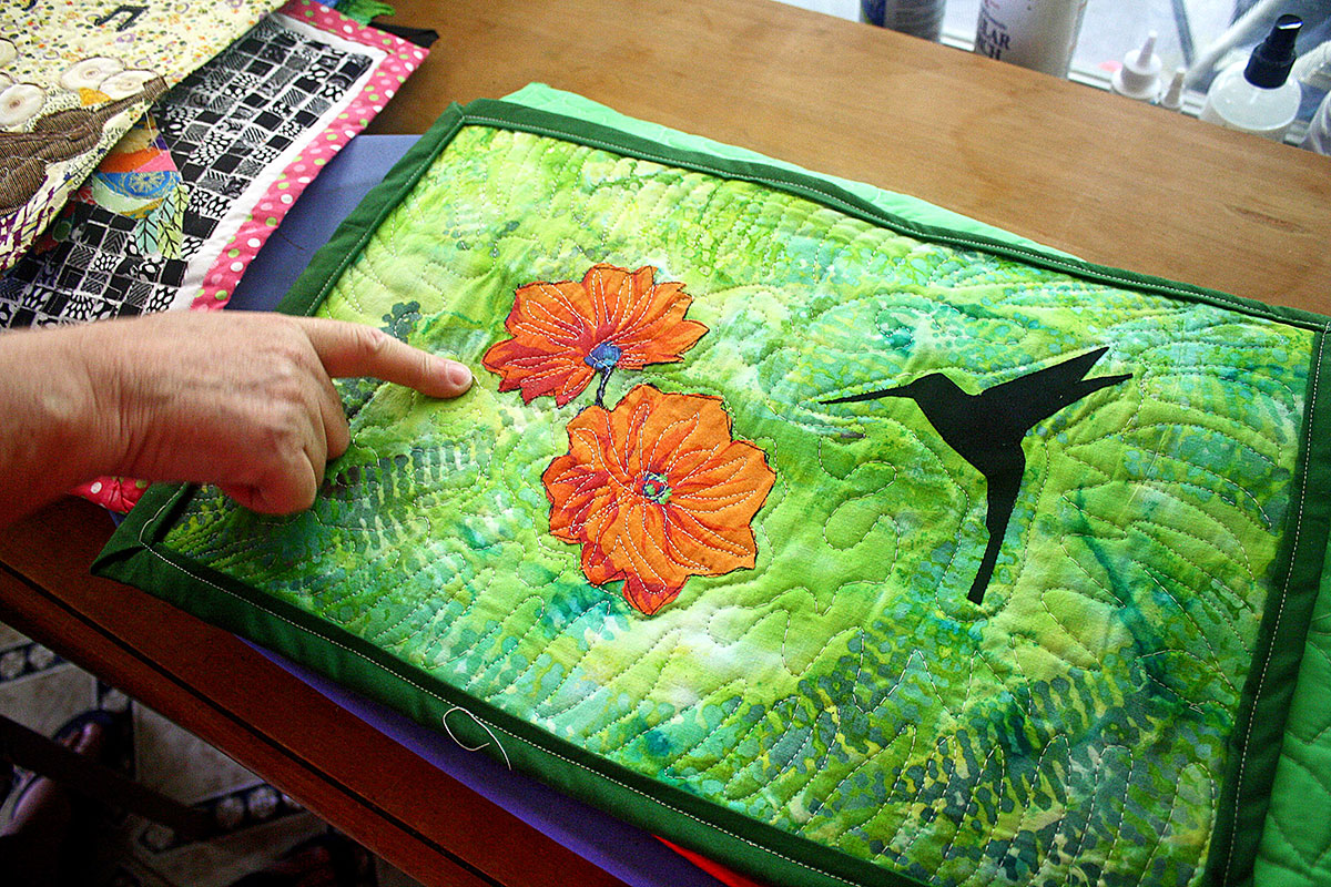 Laffont's subject choices reflect her deep concern for the environment. In this quilt, you can see the intricate free-form quilting lines that accentuate the flower applique and mimic the fern pattern of the fabric.