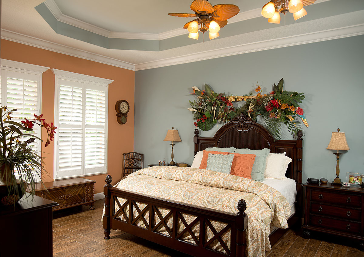 Two ceiling fans cool the master bedroom with its mixed paint scheme, crown molding and a coffered ceiling painted to look like the sky.