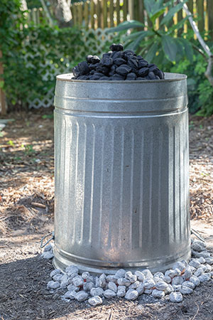 The trash can is placed over the turkey, surrounded and topped by coals.