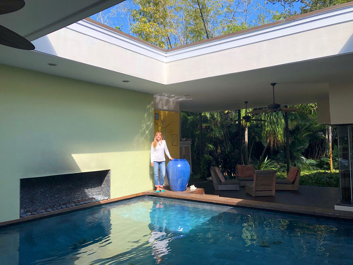 Holly Brennan stands by the pool at her Vero Beach home